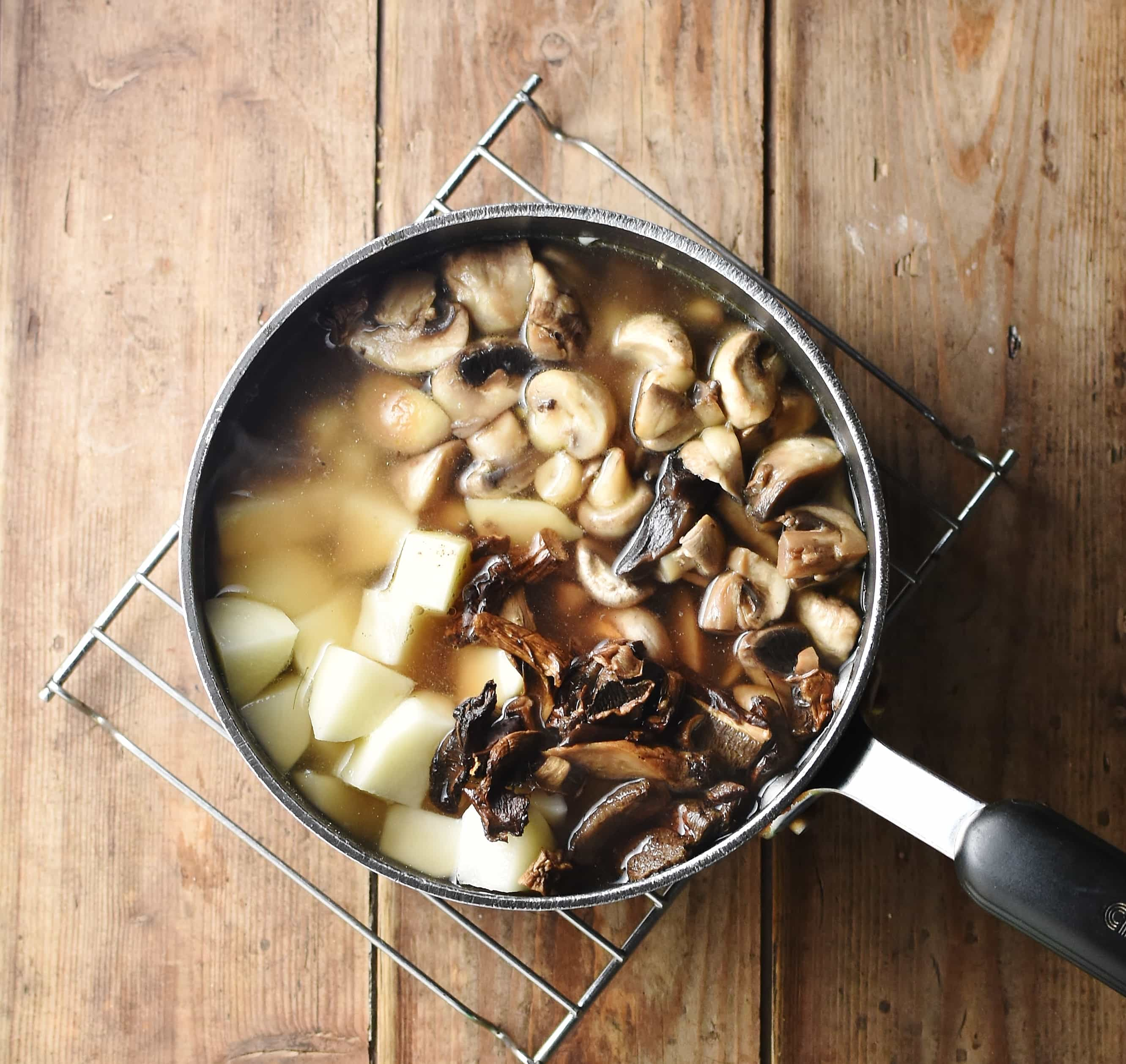 Mushrooms and cubed potatoes in large pot with water.