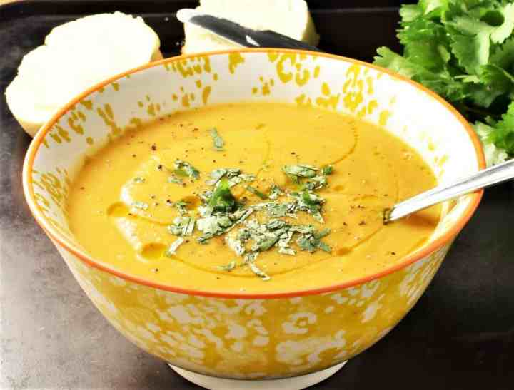 Side view of creamy lentil and butternut squash soup in yellow bowl with bread in background.
