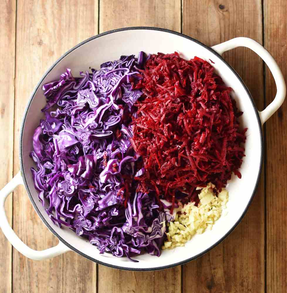 Shredded red cabbage, grated beetroot and chopped ginger in large white pan.