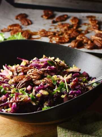 Red cabbage holiday salad with pecans and herbs in black bowl with spoon, and pecans on top of baking sheet with parchment paper in background.