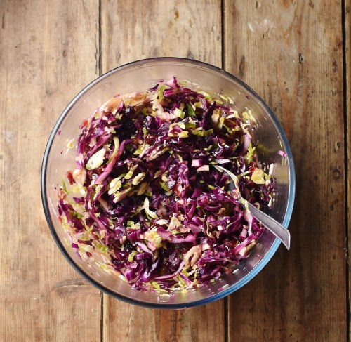Christmas slaw in mixing bowl with spoon.