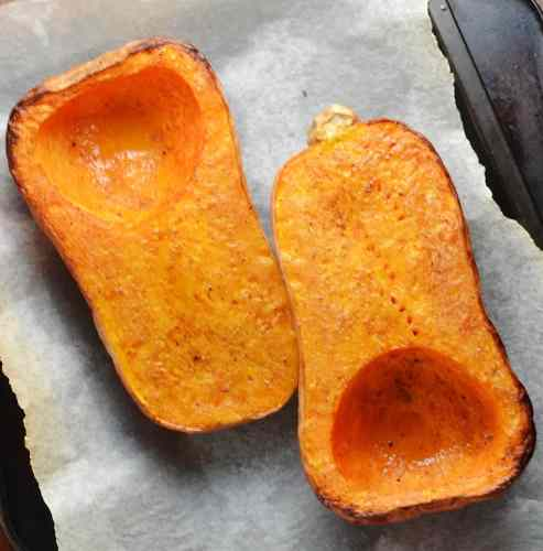 Roasted butternut squash halves on white paper.