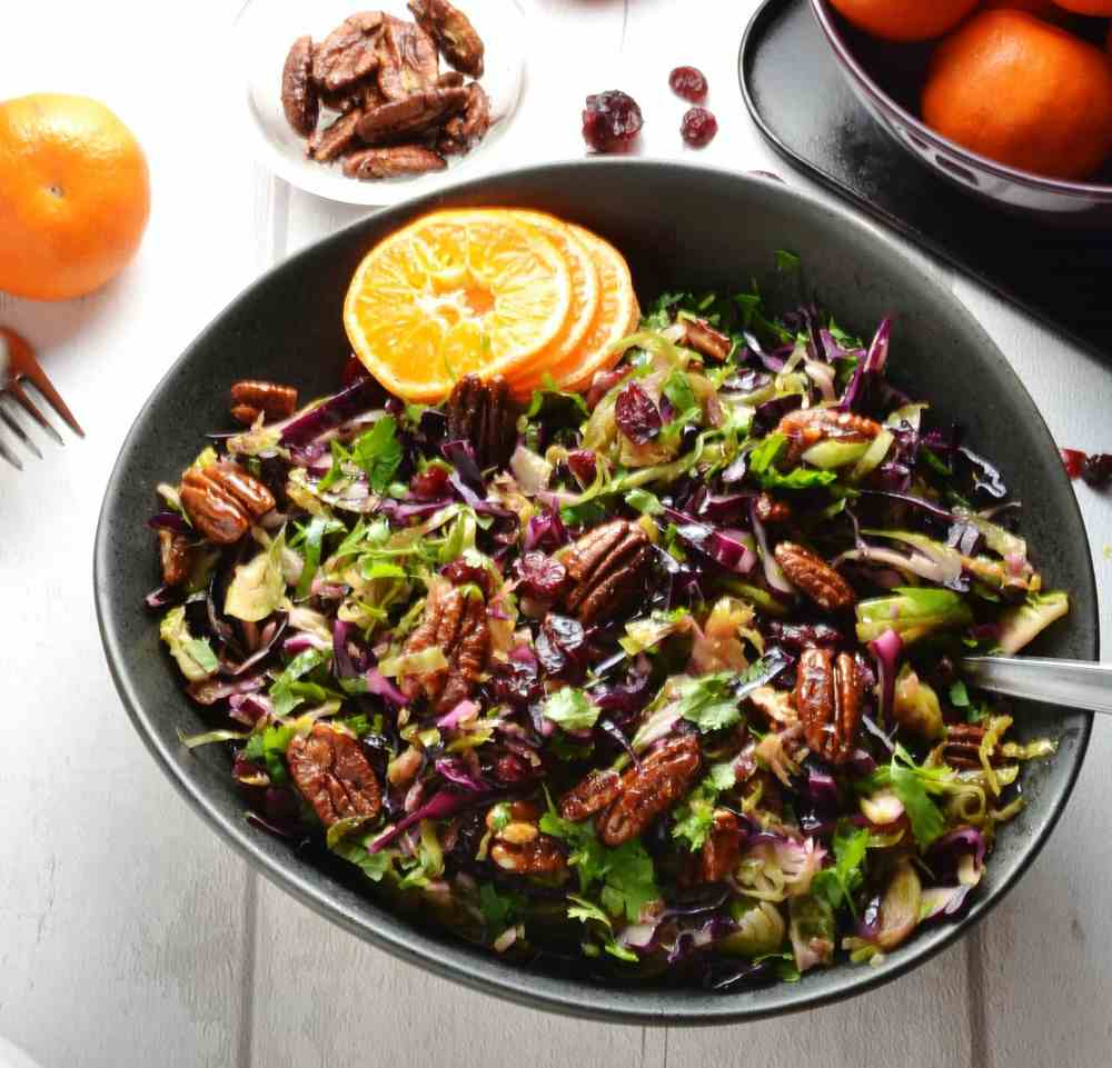 Top down view of red cabbage coleslaw in black bowl with pecans and clementine in background.