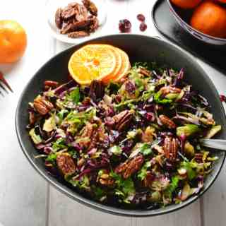 Top down view of Christmas slaw in black bowl with pecans and clementine in background.