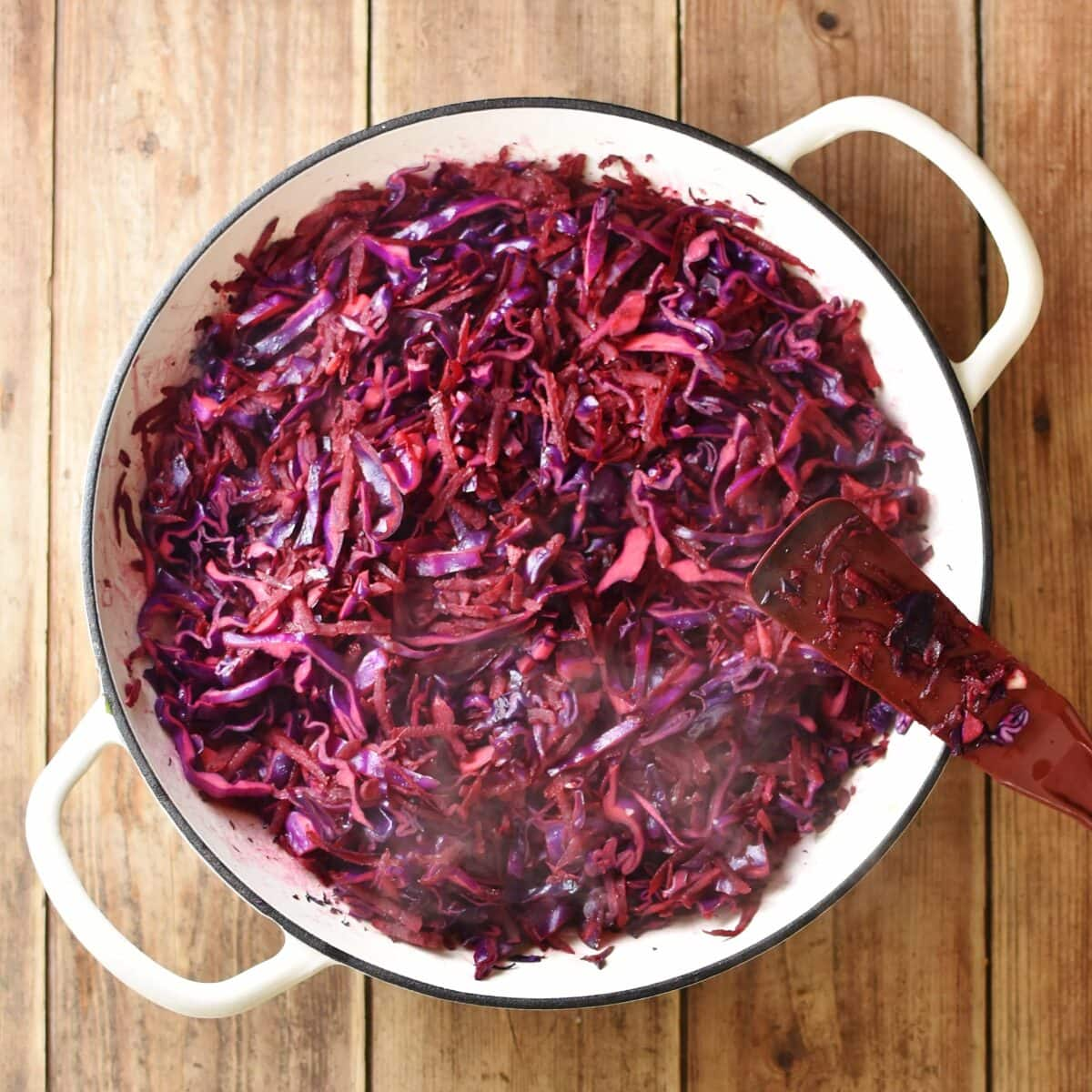 Braise shredded red cabbage with red spatula in large white pan.