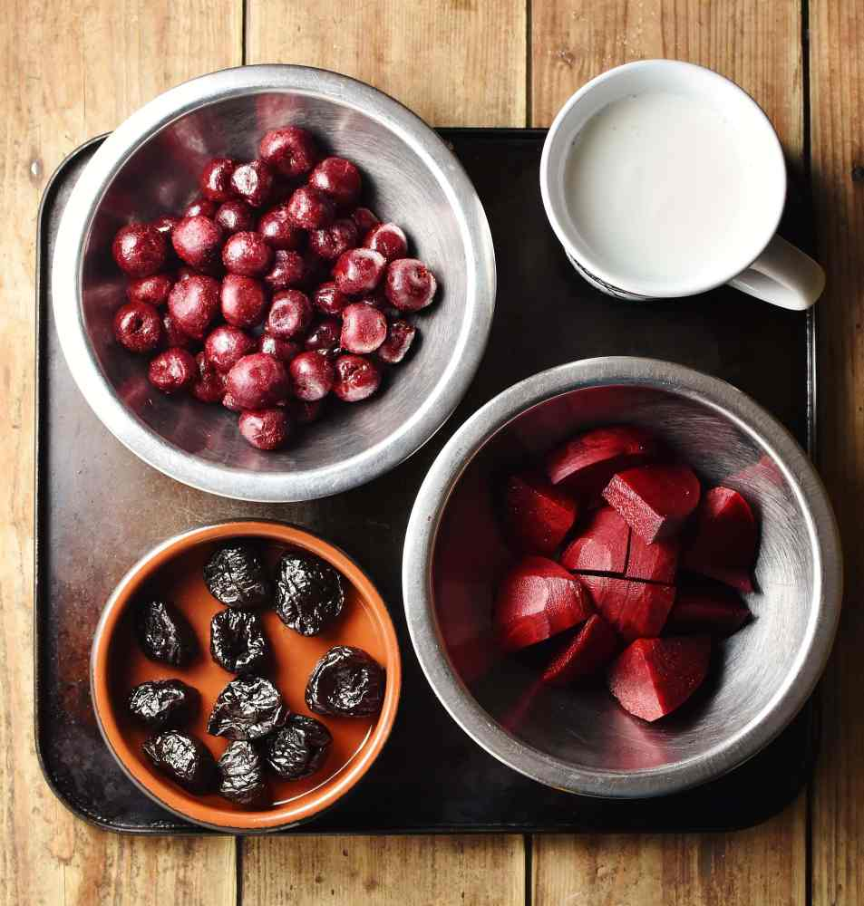 Cherries, cubed beetroot and prunes in separate bowls and kefir in cup.