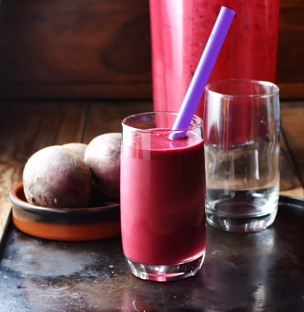 Side view of beetroot smoothie with purple straw in glass, with empty glass, beetroot in brown dish and blender in background.
