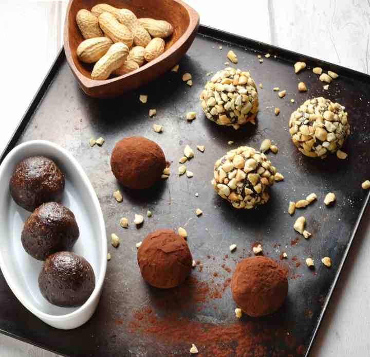 Chocolate energy balls coated with cocoa and crushed peanuts on top of oven tray with white oval dish.