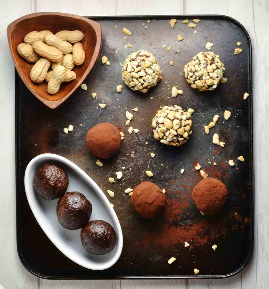 Top down view of nut and cocoa coated energy balls in white dish with peanuts in brown dish on top of dark tray.