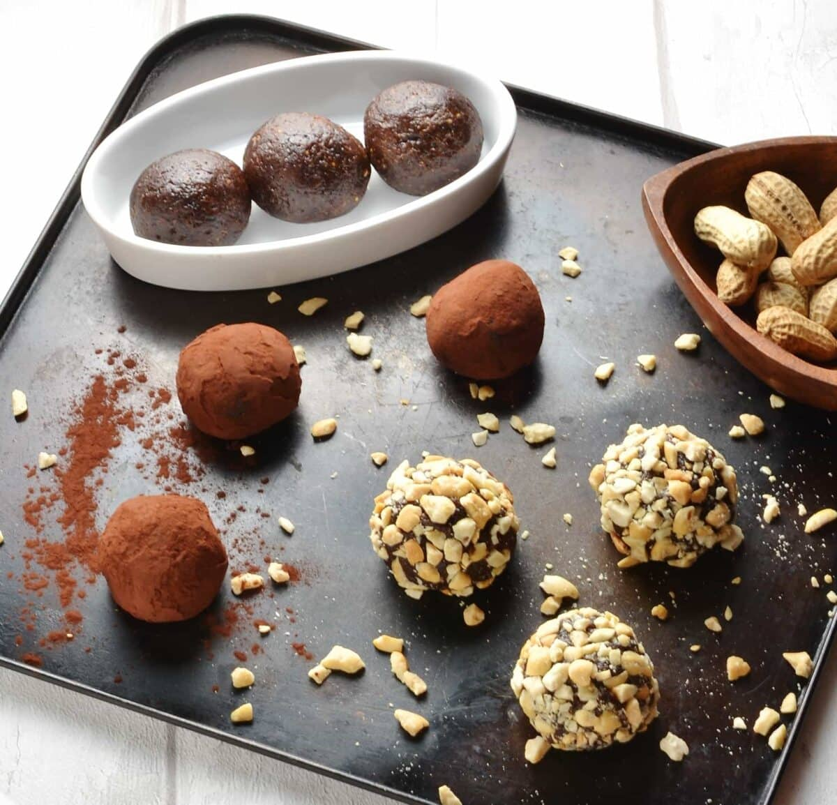 Side view of chocolate energy balls coated in cocoa and crushed nuts on metallic tray.