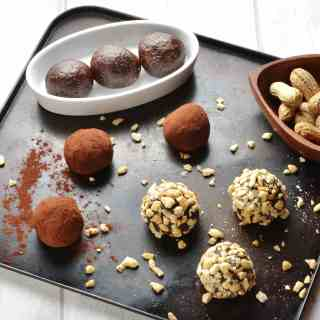 Side view of Chocolate Peanut Butter Energy Balls coated in cocoa and crushed nuts on oven tray.