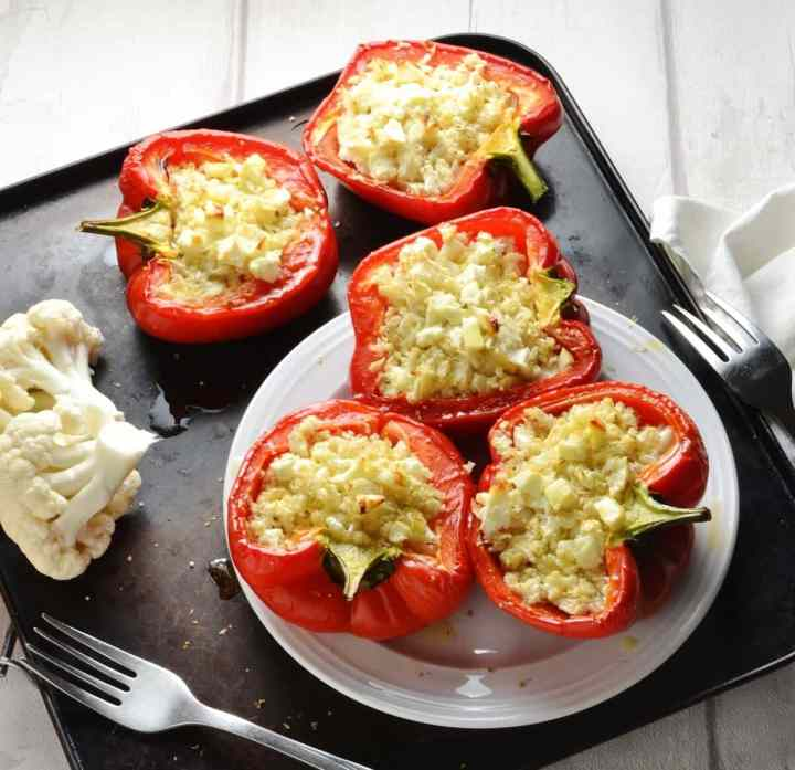 Cauliflower rice stuffed peppers on white plate with cauliflower florets and forks on oven tray.