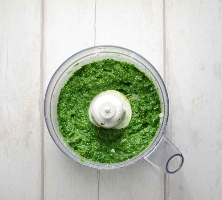 Top down view of spinach filling mixture in blender bowl on white wood background.