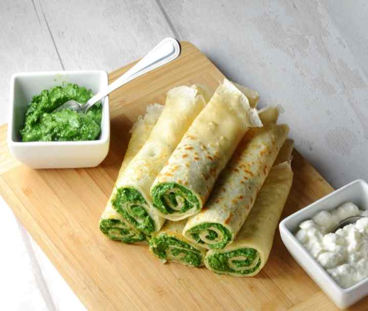 Crepes with spinach on wooden board with cottage cheese in white dish in bottom right corner and spinach mixture with spoon in white dish to left.