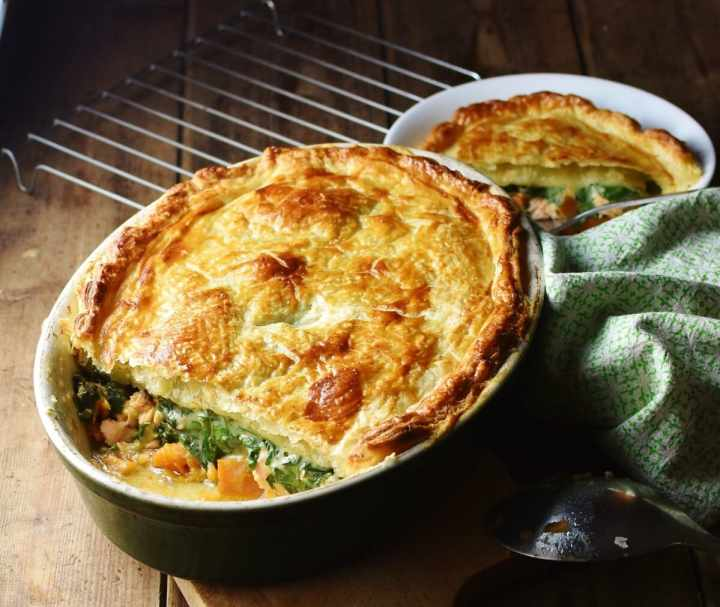 Side view of salmon spinach pie with golden puff pastry on top in oval dish, with green cloth to the right and pie portion in white bowl in background.