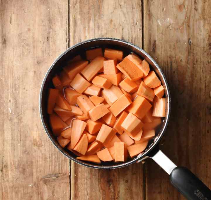 Cubed peeled sweet potato in saucepan with water.