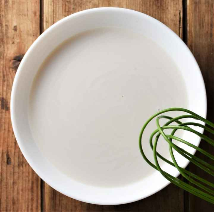 Milk mixture in white bowl with green whisk.