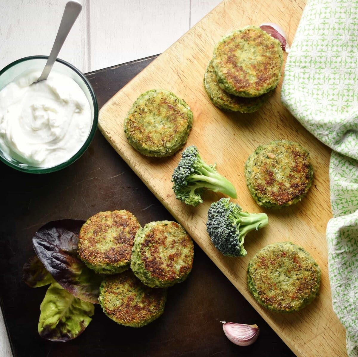 Top down view of broccoli cakes on dark tray and wooden board with broccoli florets, garlic clove, yogurt in small dish with spoon to left and green cloth to right.