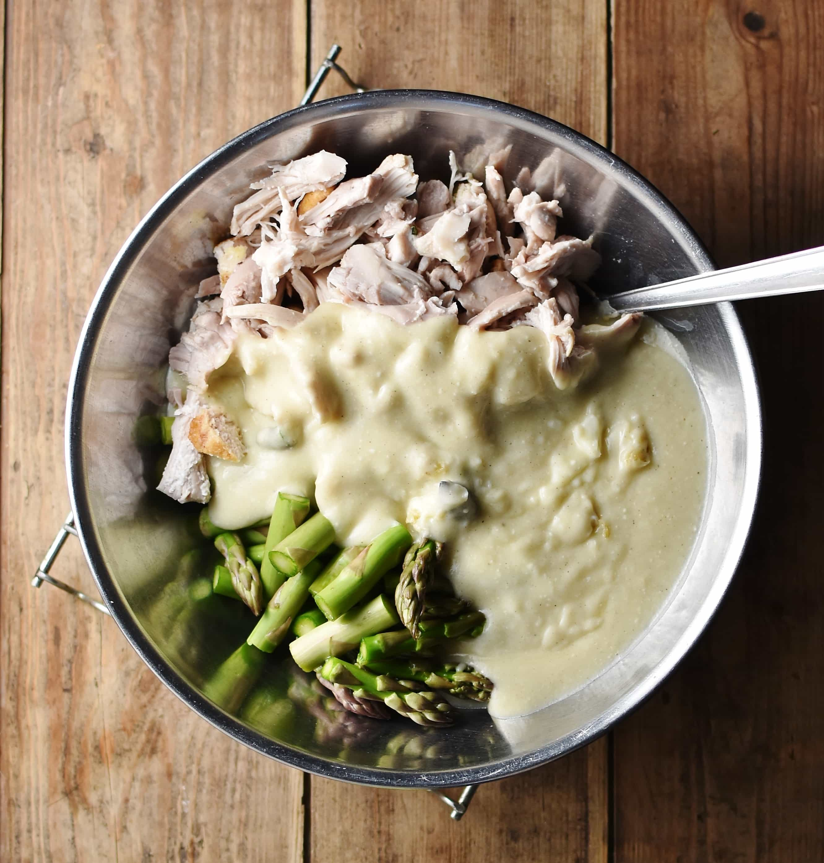 Chopped asparagus, shredded chicken and creamy sauce with spoon in large metal bowl.