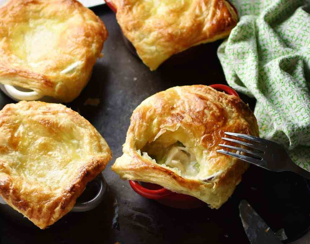 Close-up view of mini chicken pies with fork and green cloth to right on top of dark tray.