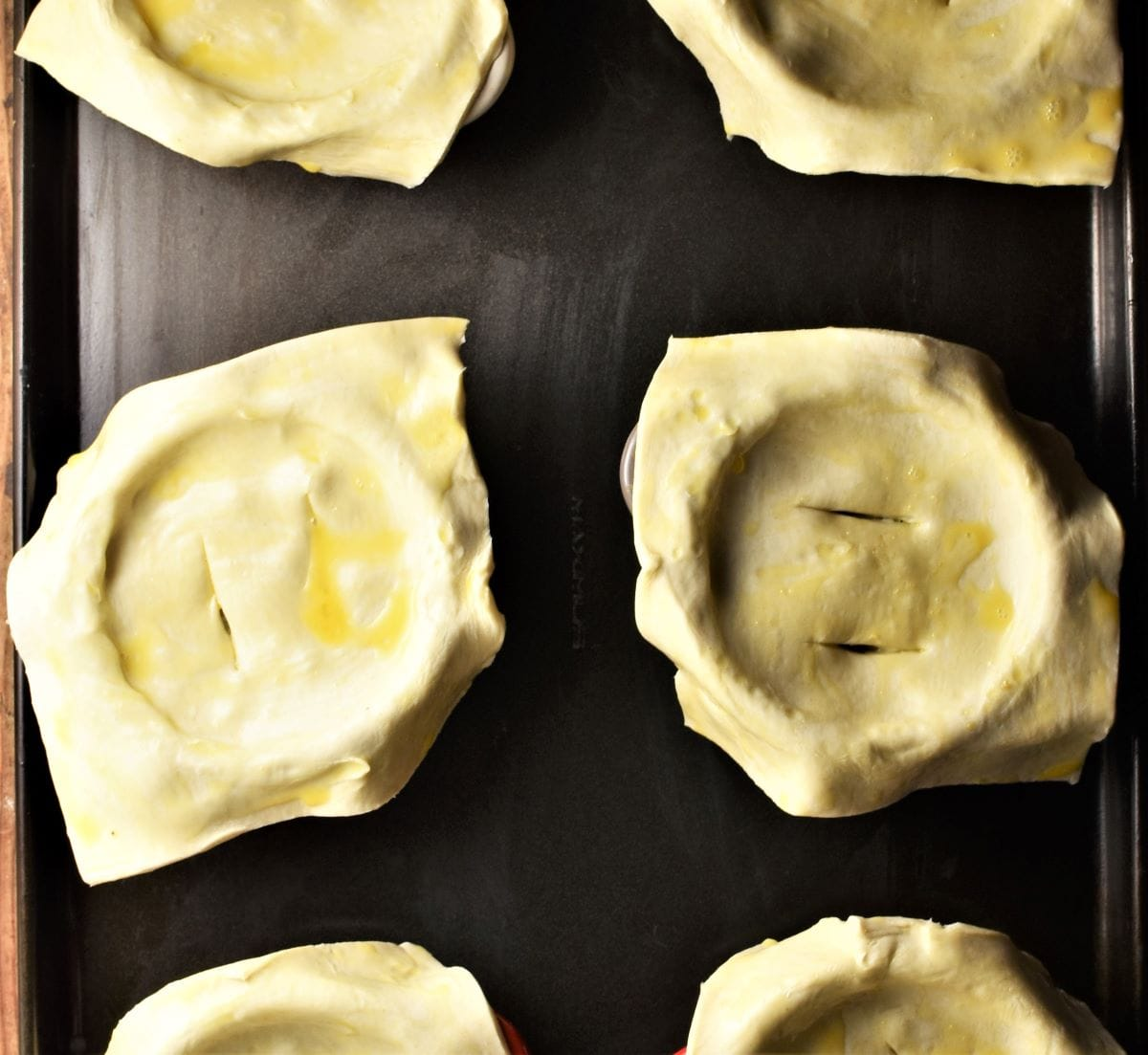 Uncooked pies with pastry squares on top.