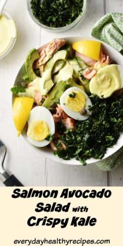 Top down partial view of salmon avocado, egg and kale salad in white bowl, with crispy kale in white dish in background.