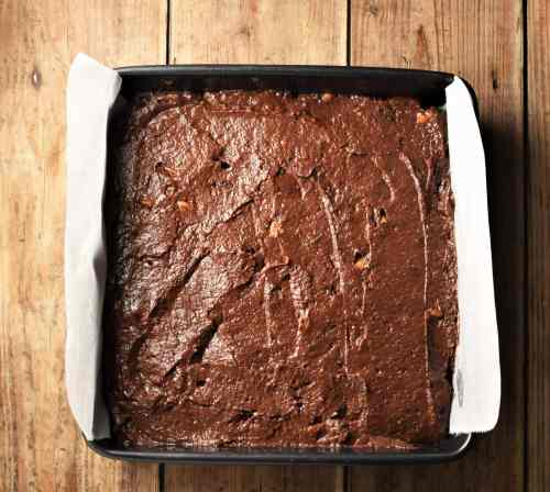 Brownie cake batter in square pan lined with parchment paper.