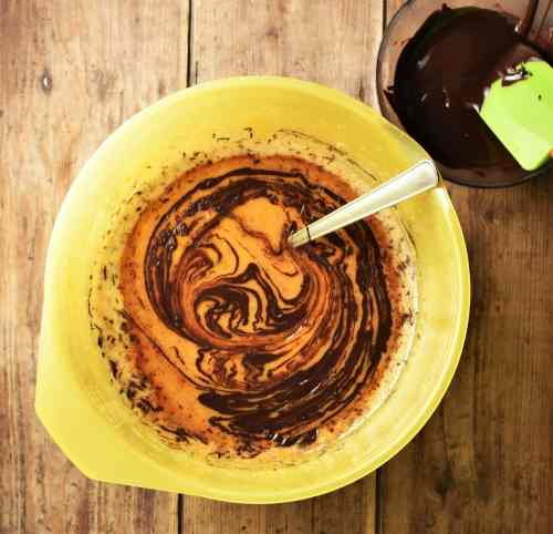 Sweet potato brownie mixture with melted chocolate in large yellow bowl with spoon and melted chocolate with green spatula in small dish in top right corner.