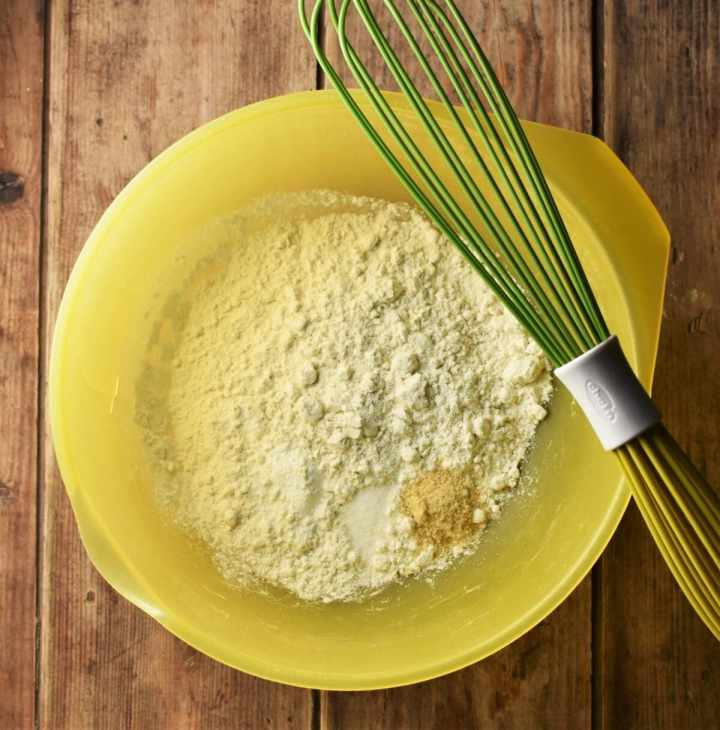 Flour mixture in large yellow bowl with green whisk.