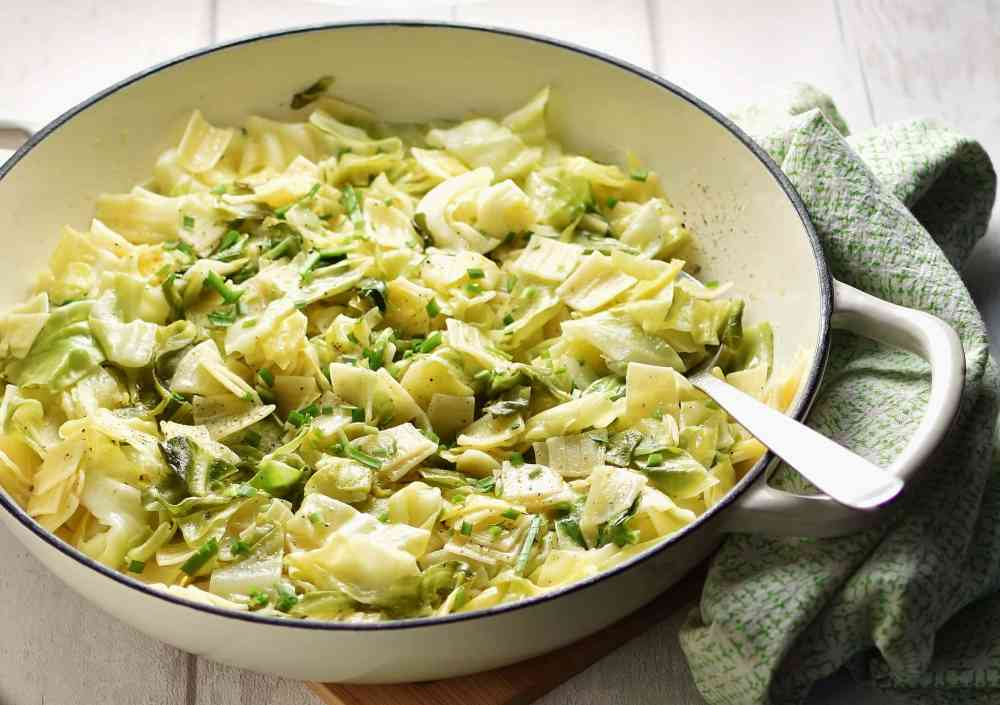Close-up partial view of pasta with cabbage and spoon inside large white dish, with green cloth to the right.