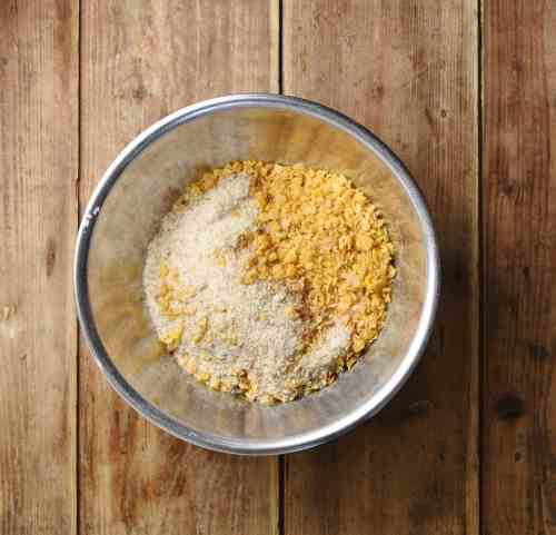 Crushed cornflakes and breadcrumbs inside metal bowl.