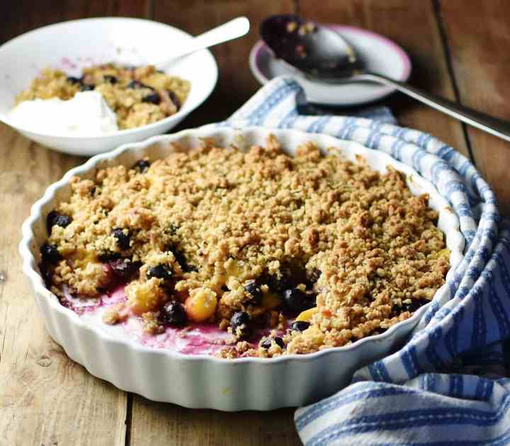 Side view of blueberry peach crisp in large white ceramic round dish wrapped in blue-and-white stripy cloth, with large spoon on top of small saucer, crumble in white bowl with spoon and yogurt in background.
