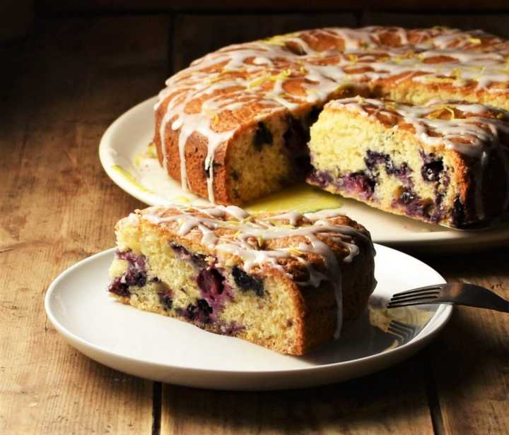 Side view of blueberry cake slice on white plate, with cake in background.