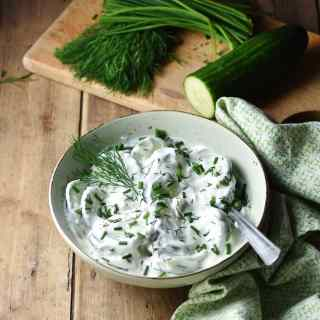 Creamy cucumber salad in green bowl with spoon wrapped in green cloth, with herbs and cucumber in background.