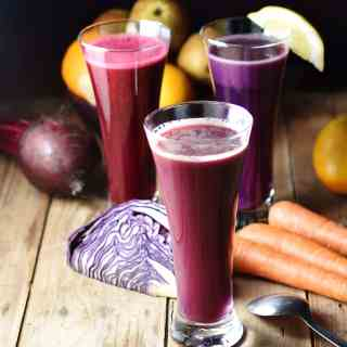 Side view of cabbage juice in 3 separate tall glasses with red cabbage, carrots, beet, and other raw vegetables and fruits in background on top of wooden board with spoon to the right.