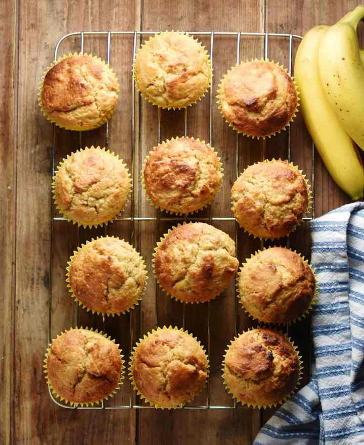 Top down view of banana muffins on top of cooling rack with bananas in top right corner and stripy blue-and-white cloth to the right.