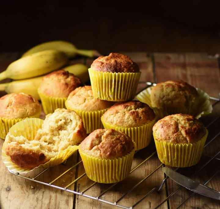 Side view of banana muffins in yellow paper cases on top of cooling rack with bananas in background.