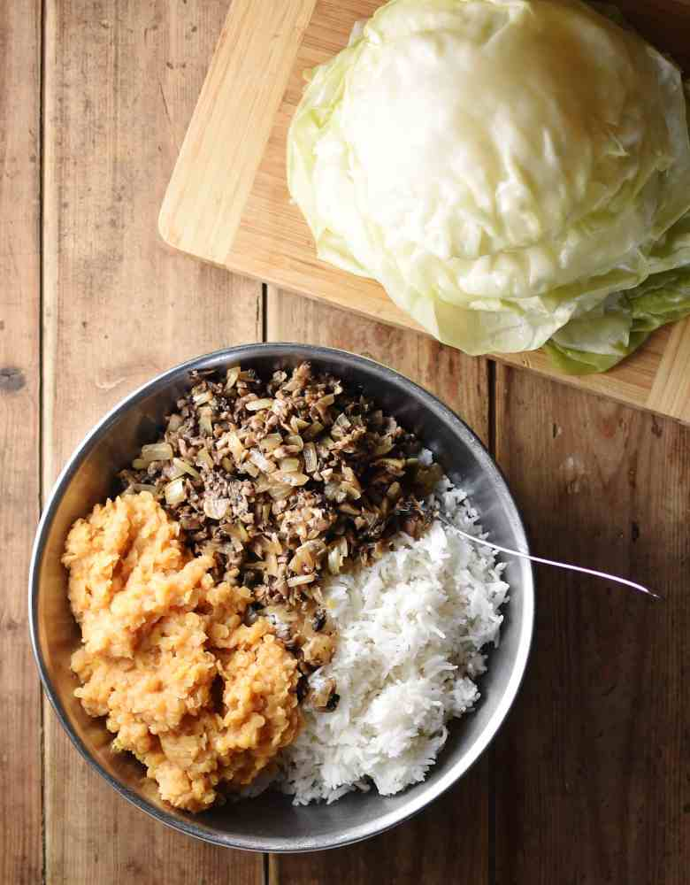 Top down view of rice, lentils and mushrooms in bowl, with cabbage leaves on top of cutting board.