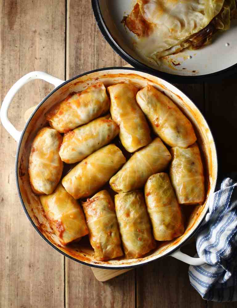 Top down view of cabbage rolls in large white dish with lid in top right corner and blue-and-white cloth in bottom right.