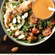 Top down view of grilled chicken, spinach, quinoa and tomato salad with orange coloured dressing in small dish with white spoon inside green bowl.