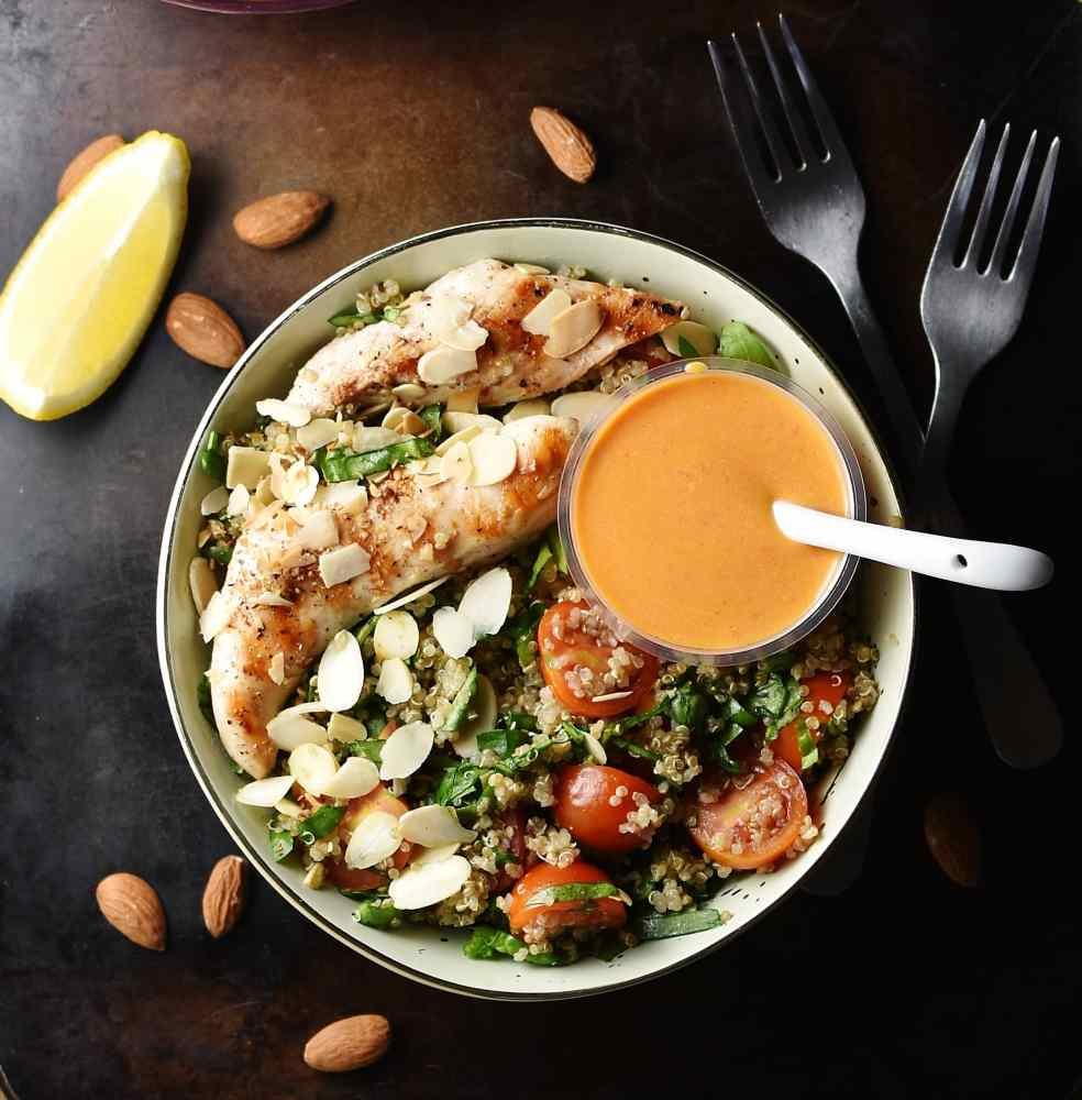 Grilled chicken strips, quinoa, cherry tomatoes and almond flakes with small dish with dressing and white spoon inside white bowl, with 2 forks, almonds and lemon wedge in background.