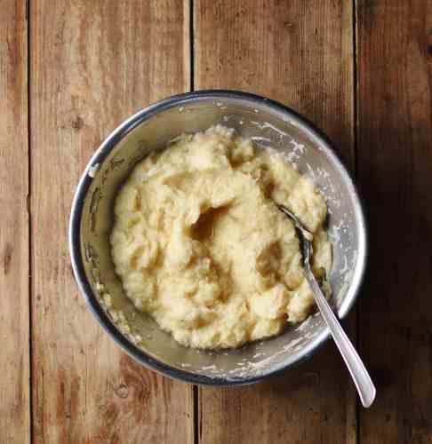 Potato pancake batter with spoon inside metal bowl.