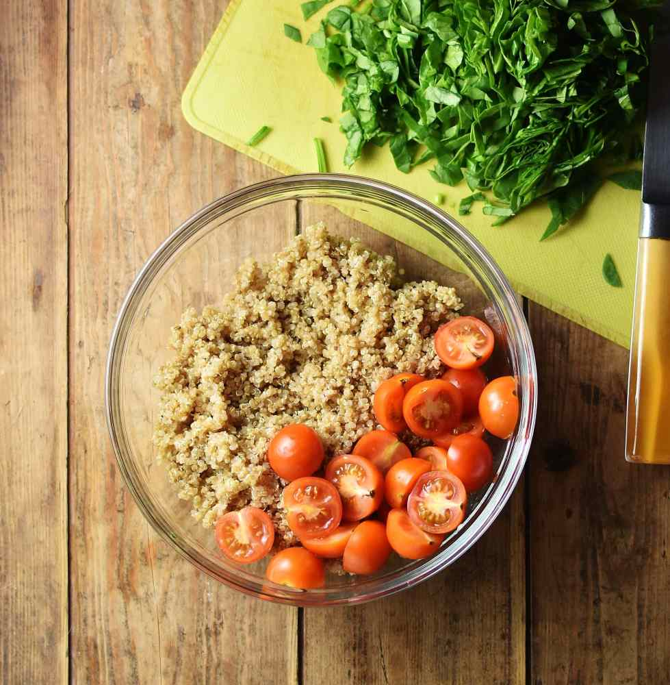 Cherry tomatoes and cooked quinoa in large bowl, with chopped spinach on yellow cutting board.