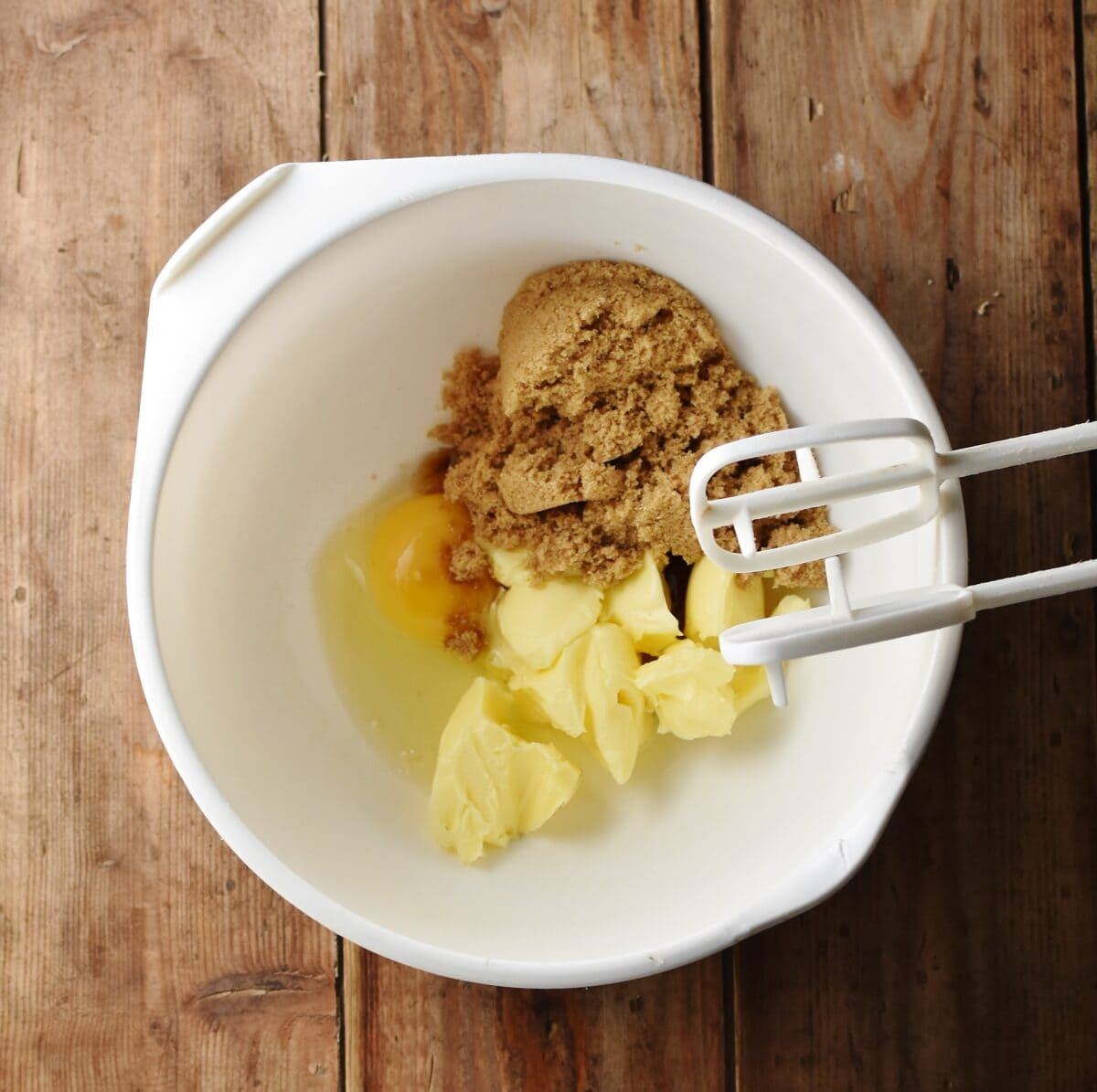 Egg, brown sugar and butter in large white bowl with electric mixer end bits.