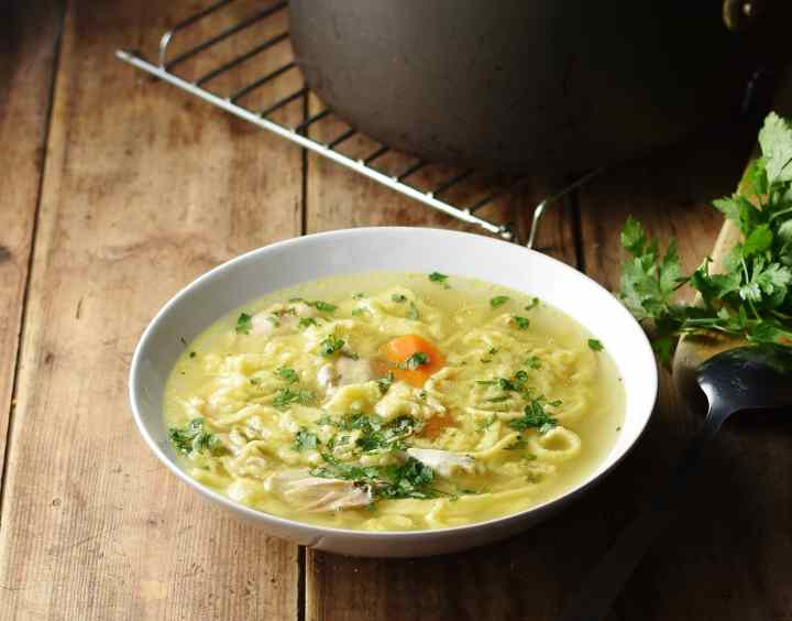 Side view of chicken egg drop noodle soup in white bowl with pot on cooling rack in background.