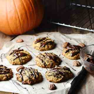 Pumpkin cookies with chocolate drizzle on top of paper with pecans, and pumpkin in background.