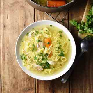 Chicken egg drop noodle soup in white bowl with spoon and parsley to right and partial view of pot at the top.