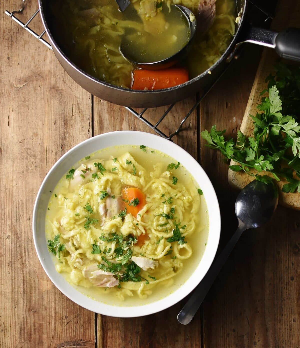Egg drop noodles chicken soup with parsley in white bowl, with spoon and parsley to the right and soup in top at the top.
