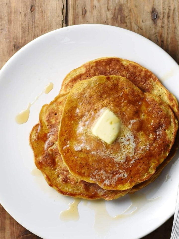 Pancakes with know of melting butter on top and fork to the right on white plate.