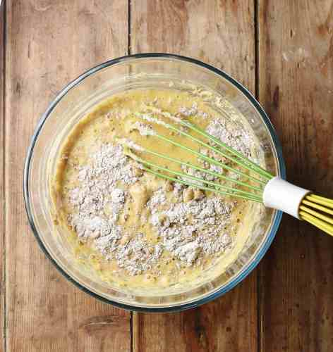 Pancake batter with some flour still visible in mixing bowl with green whisk.